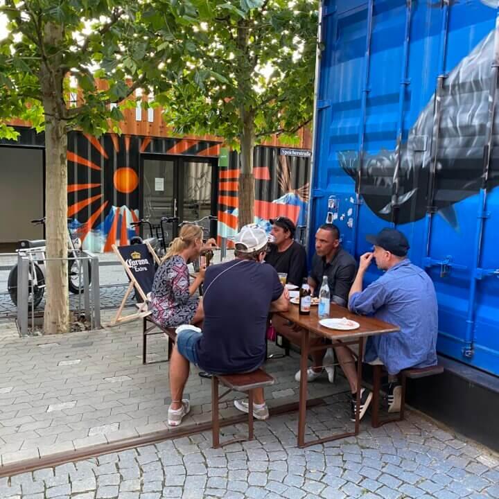 Gruppe sitzt auf einer Bierbank vorm Container Urban Bike Tours