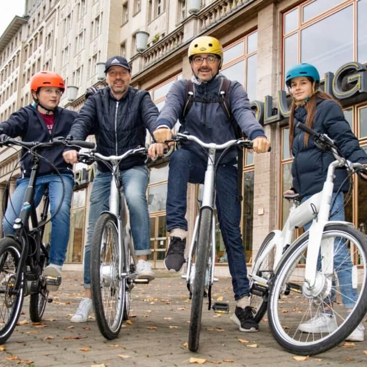 famile auf e-bikes vor der karl-marx buchhandlung in berlin