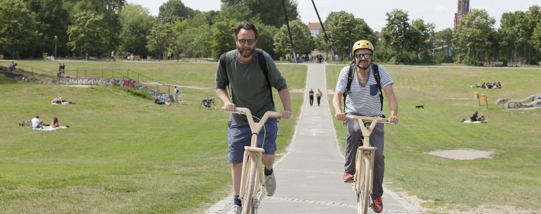 Heinz and JR from Urban Bike Tours ride through Görlitzer Park on 2 wooden bikes from cocomat.bike