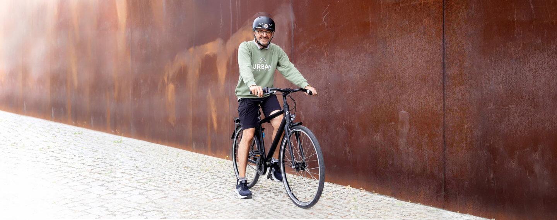 Mann auf Stadtrad Agatu Light vor roter Mauer