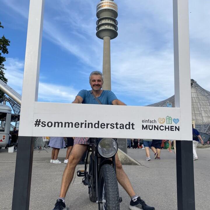 Heinz Guide bei Urban Bike Tours schaut durch einen Fotorahmen für ein Bild mit Fernsehturm