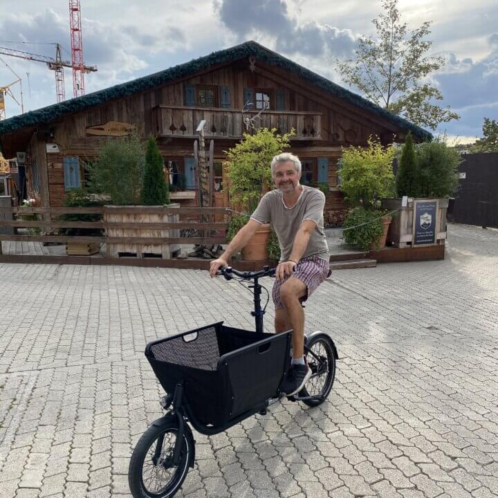 Muli Lastenrad steht mit Fahrer vor der knödelalm im Werksviertel in München