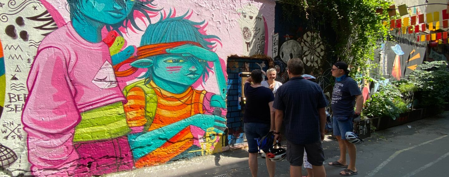 small group of cyclists in front of grafiti house schwarzenberg