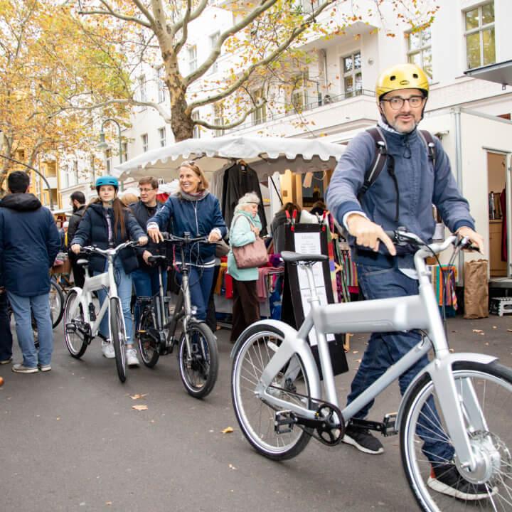 Heinz Gründer von Urban bike tours geht mit einer kleinen Gruppe über den Kollwitzplatz