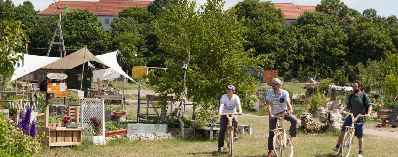 3 Personen mit Holzrädern vor den Allmende Gärten auf dem Tempelhofer Feld